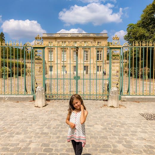 Little girl standing in front of the Trianon Palace Versailles