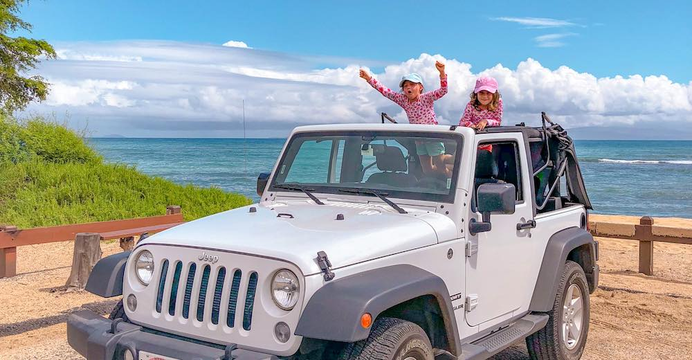 Two girls cheering from the soft top of a Jeep Wrangler at a Maui beach