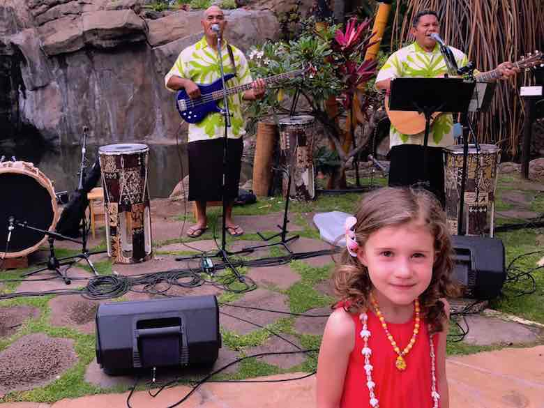 A little girl having her picture taken with a performing band at the Maui luau