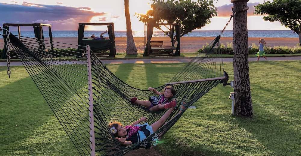 Two girl lounging in a hammock at Ka'anapali beach in Maui