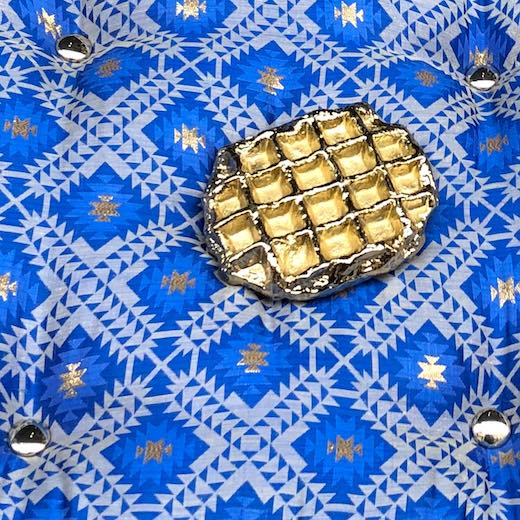 Golden waffle on a patterned blue cushion