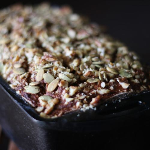 Paleo Banana Bread - Moist banana bread topped with crunchy nuts & seeds. Get the recipe from Cosmopolitan Cornbread.