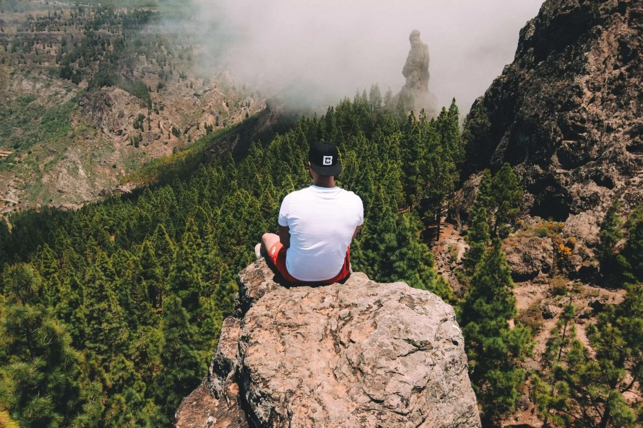 Man standing on a cliff, watching the mountains.