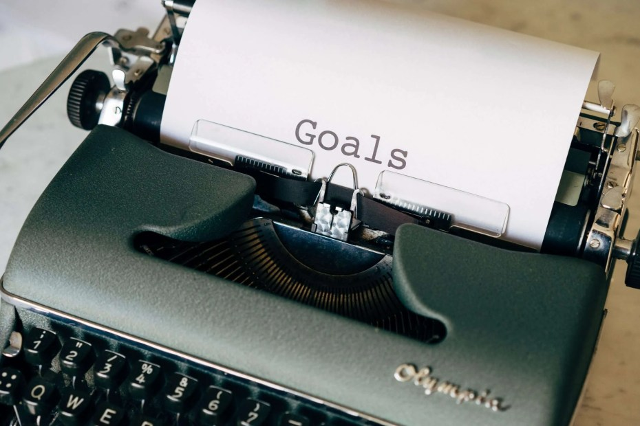 """A writing machine with the word """"goals"""" written on the paper. These are 4 Tips to Abandon Your Toxic Time Frame Thinking."""