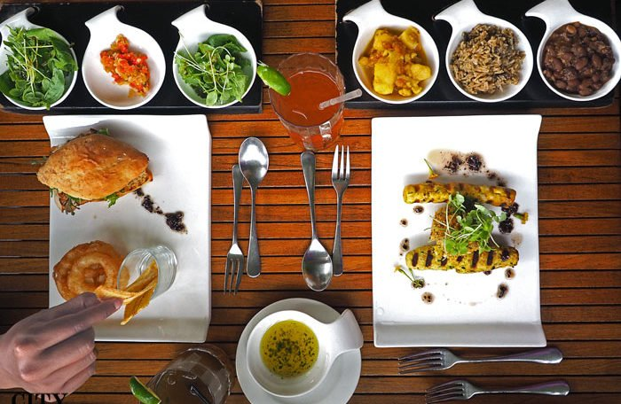 An overhead shot of a meal at Bouchan restaurant, showing the main dish surrounded by colourful side dishes