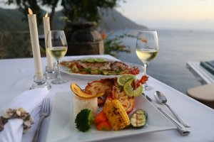 A dinner table set with a plate full of barbequed lobster and fresh vegetables, with a view of the Carribean sea in the background