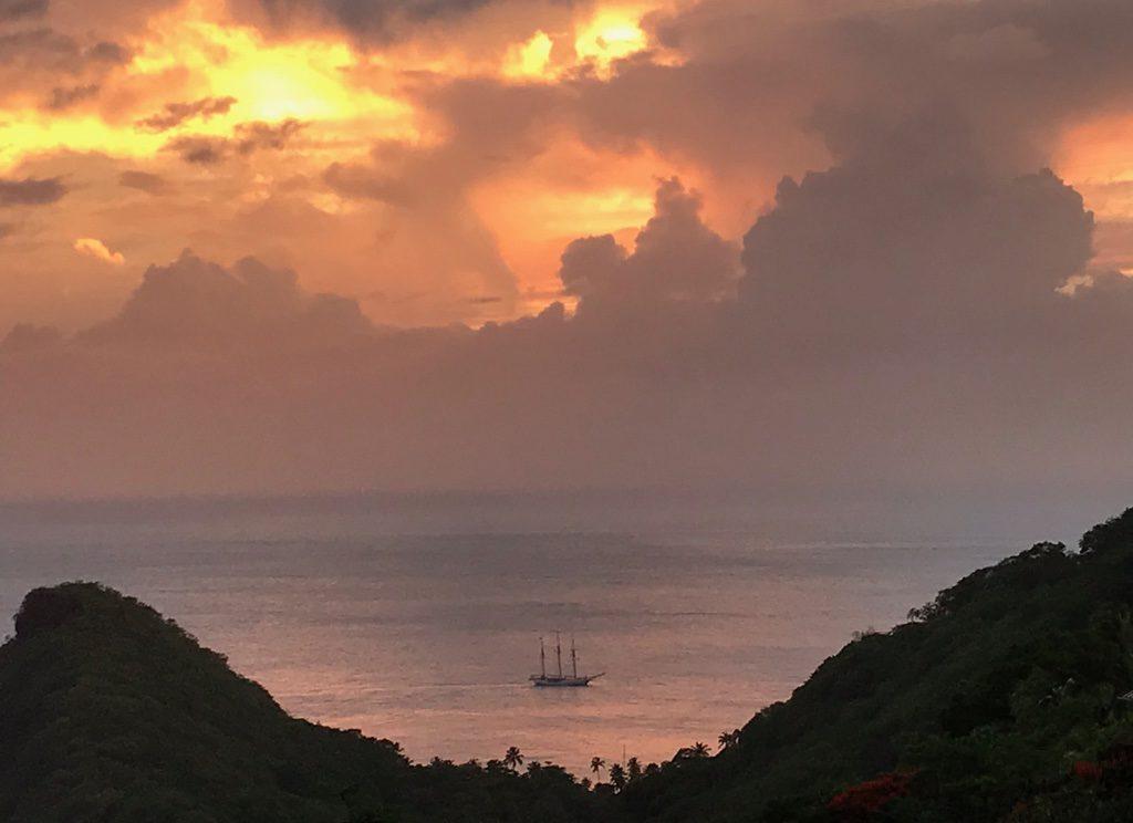 A yacht on the Carribean sea, infront of a peach sunset sky