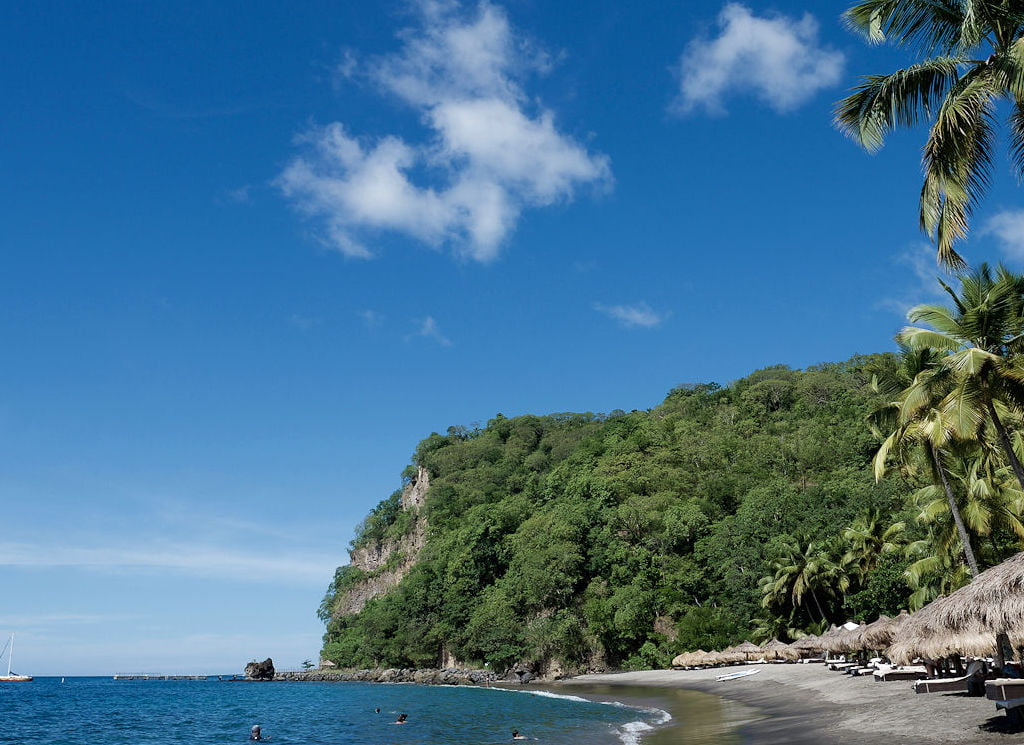 A blue sky above the cliffs covered in lush greenery next to the beach dotted with palm roofed parasols