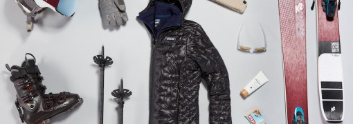 All ski gear laid out including jacket, skis, hat, boots, and more