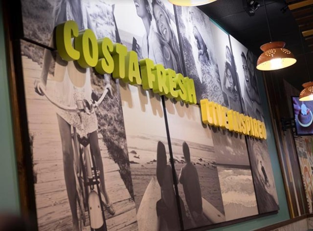 """A sign on the wall of a Costa Vida restaurant reads """"Costa Fresh. Live Inspired."""""""