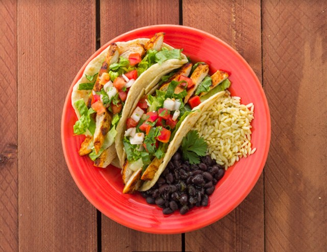 Two chicken tacos topped with pico de gallo and shredded lettuce, accompanied by a side of black beans and rice, sit on a red plate on a wooden table.