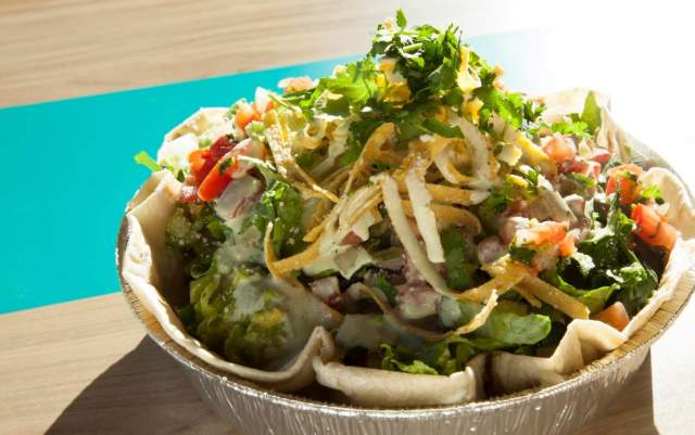 A taco salad in an aluminum tin on a wooden table is covered in garnishes, dressing, tortilla strips and salsa, as the sun lights it from behind.