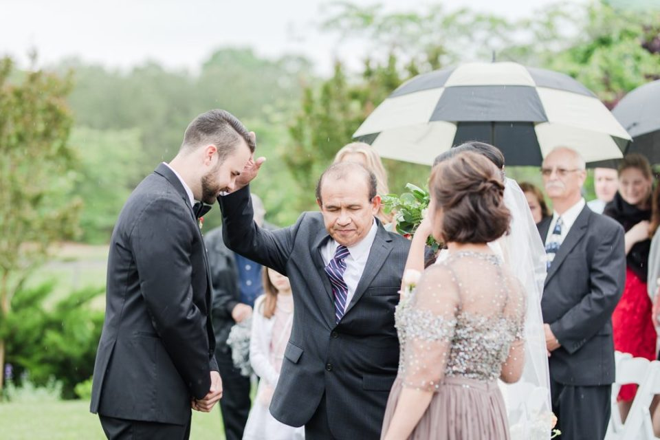 wedding ceremony in the rain at flora corner farm photographed by costola photography