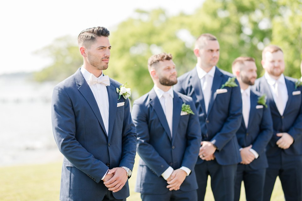 groom at ceremony at weatherly waterfront farm photography by costola photography