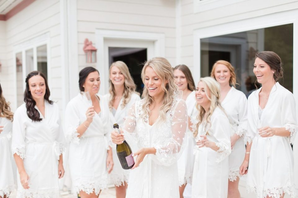 popping champagne all white bridesmaids robes at southern wedding by Costola Photography