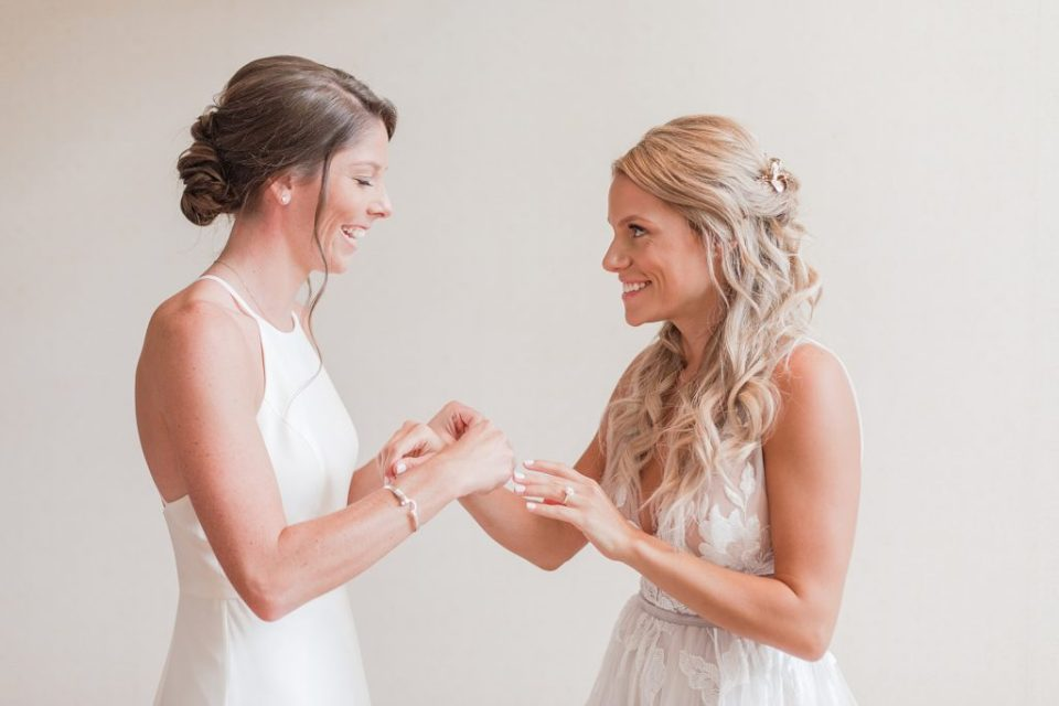 Bride getting dressed by Costola Photography