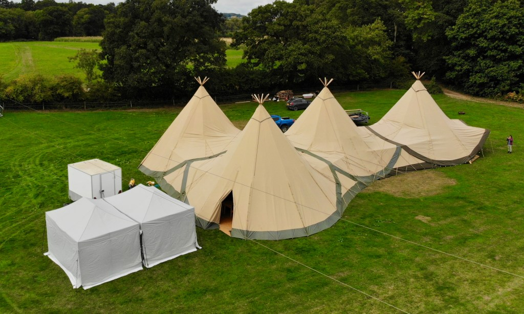 Bird's Eye view of 4 Giant Hat Tipis linked together for a tipi woodland wedding with catering tents