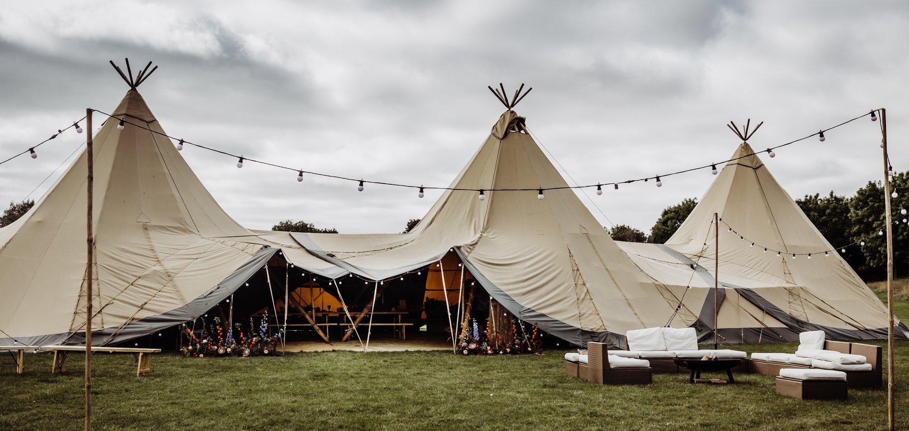 3 Giant Hat Tipis set up in a line with outdoor seating, fire pit and festoon lights on wooden poles