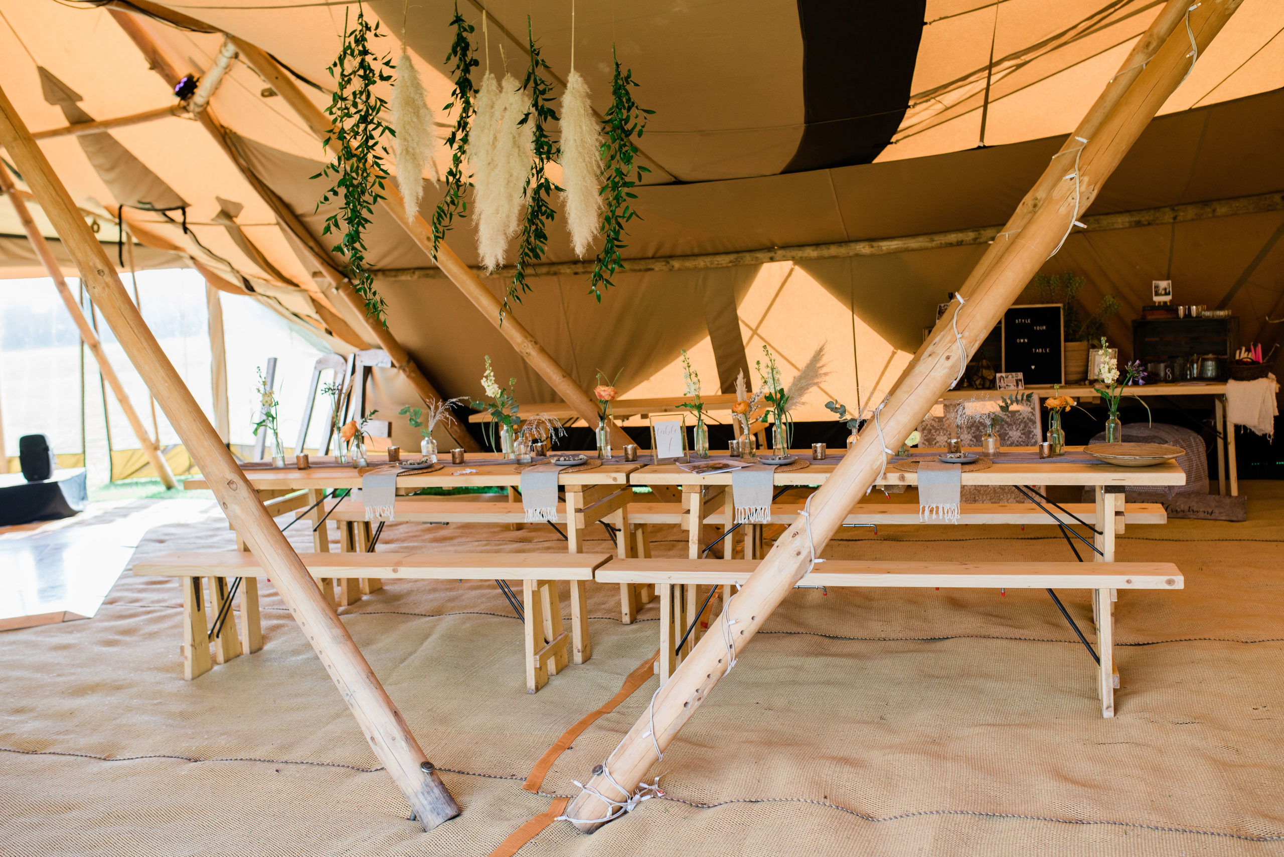 Image of 12-16 person head table in centre of 2 tipis with crystal wall tipi side extension and dance floor to the side