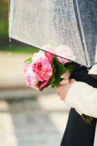 A couple on their wedding day getting caught in the rain and needing an umbrella.