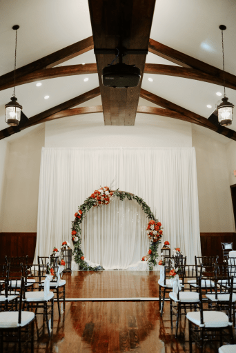 Indoor wedding venue set up featuring a large ring alter and white cloth chairs.