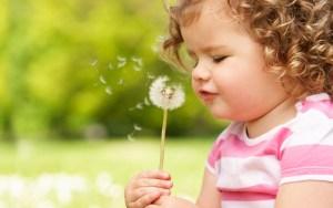 belle petite fille souffle un pisenlit