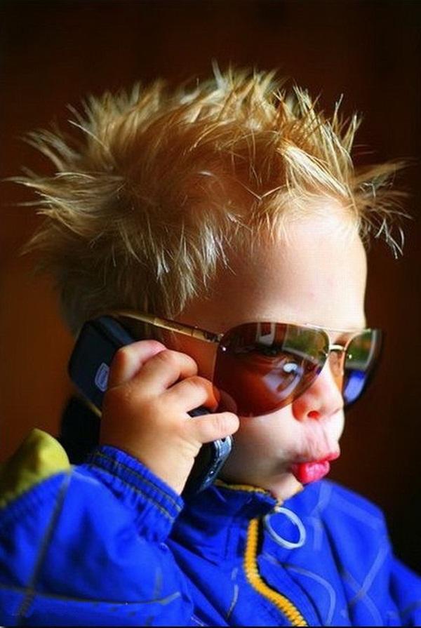 bébé cool parle au  téléphone avec des lunettes fumées