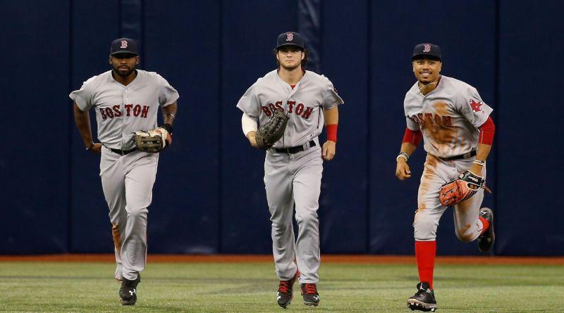 Former Red Sox outfielders Jackie Bradley Jr., Andrew Benintendi and Mookie Betts run off the field.
