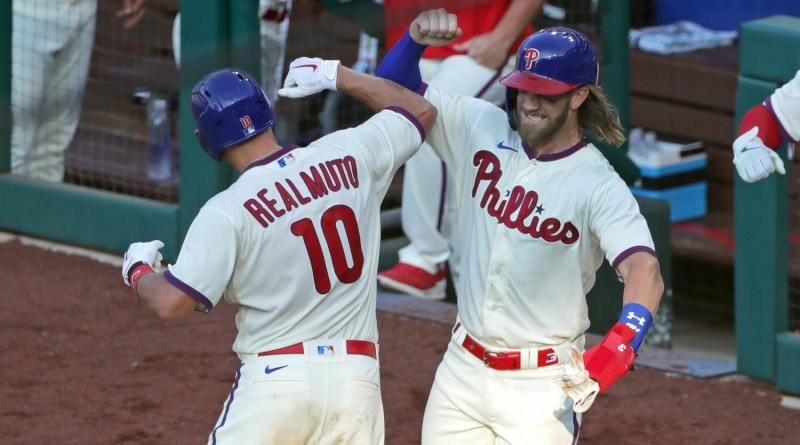 Image of Phillies Players JT Realmuto and Bryce Harper bumping forearms in their throwback uniforms