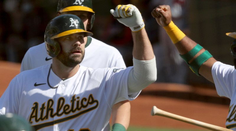Oakland Athletics designated hitter Mitch Moreland bumps fists with a teammate during a game against the Detroit Tigers