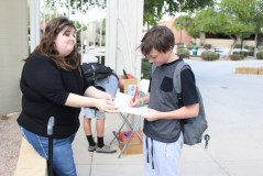 Lending a hand while Tyler Heffner, 8, votes for president, Ms. Stradling holds the clipboard. (Photo by Megan Ash)