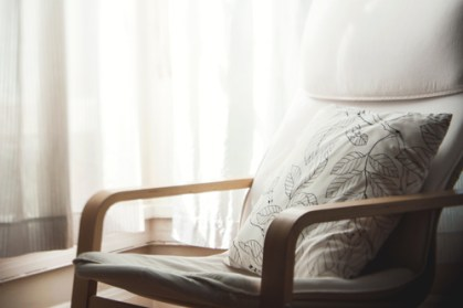 Picture of a wooden chair with fitted cushions and a single extra cushion with leaf outline pattern, in a soft lit room with pale curtains in background. Taken by Kari Shea on Unsplash