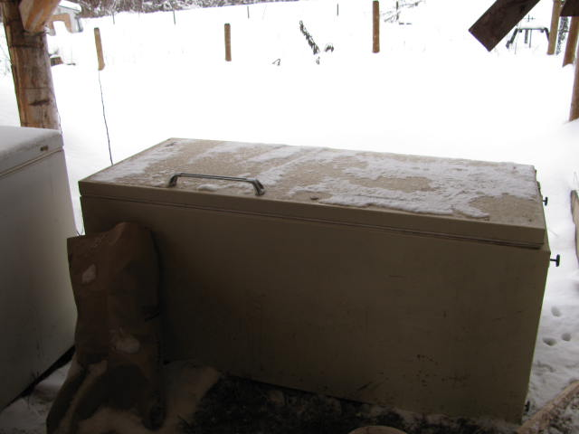 Storing animal feed in an old freezer that doesn't work anymore.