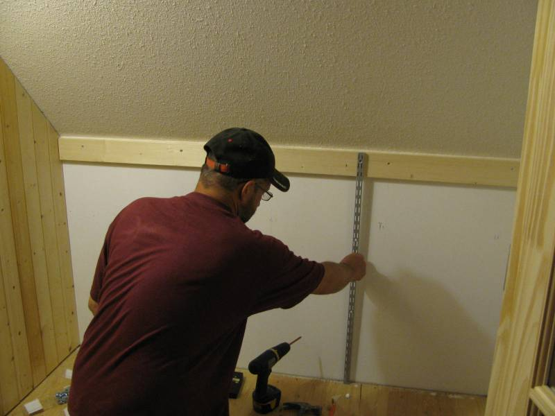 measuring for shelf track placement on back wall.