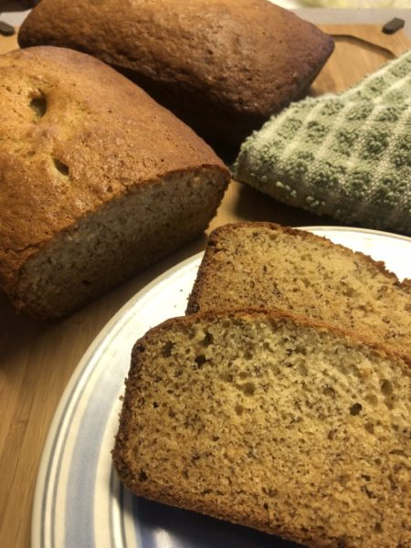 Slices of banana bread on a plate with two loaves behind them.