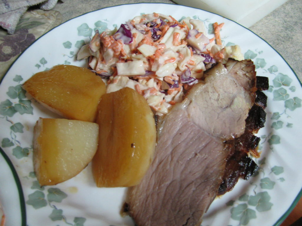 roasted ham and potatoes, with cole slaw on a dinner plate