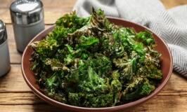 Tasty baked fresh kale chips on wooden table