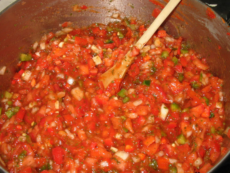 Fresh ingredients are on the stove for making and canning salsa.