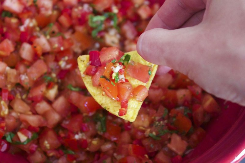 Fresh homemade Salsa sits on a taco chip ready to be eaten.