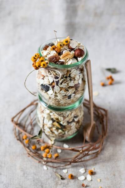 A jar full of granola decorated with flowers and twigs.