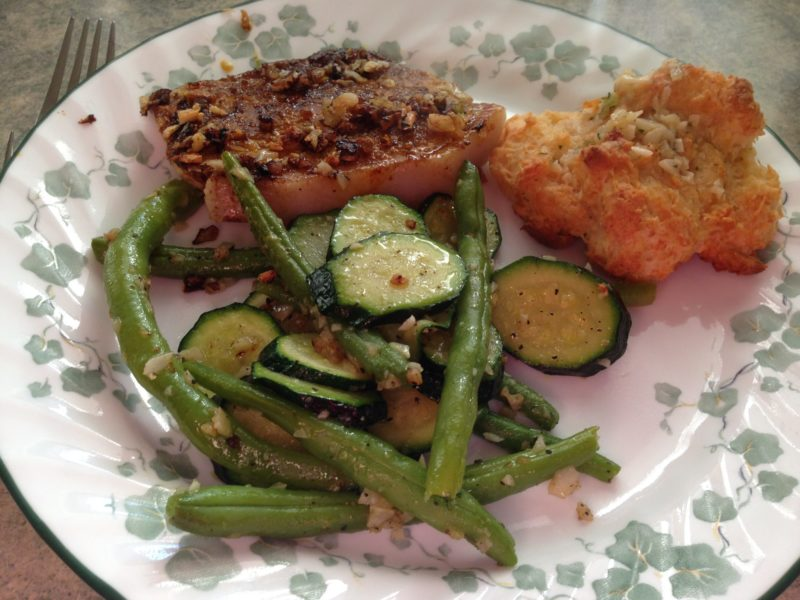Cooked pork chop on a plate with vegetables and a biscuit.