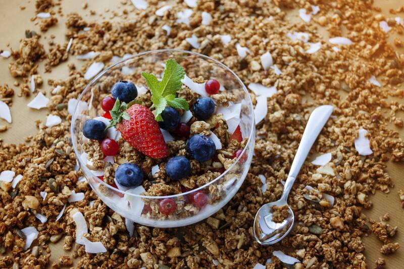 Homemade granola in a bowl with yogurt and berries.