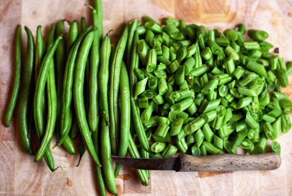 cut green beans sit on a cutting board