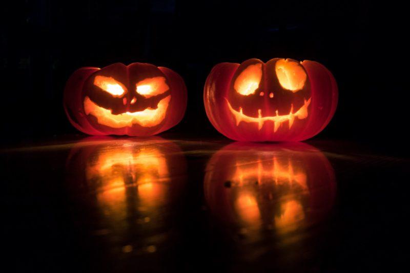 Lit pumpkins sit in the dark.