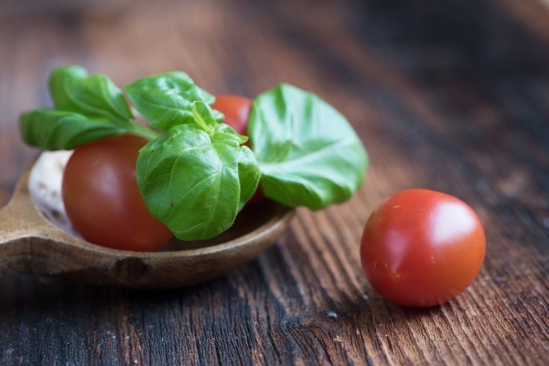 Fresh basil and tomatoes sit on a cutting board.