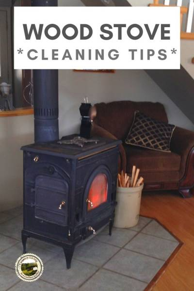 a burning wood stove sits on a tile hearth