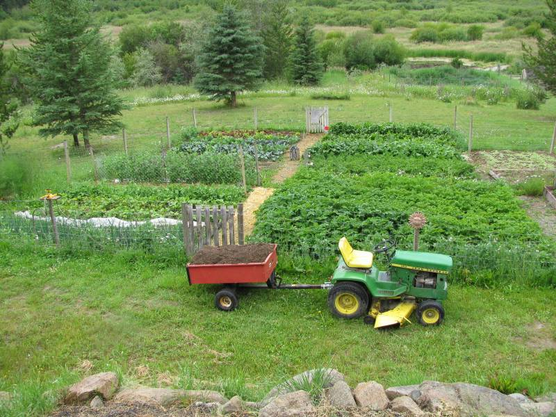 a tractor sits just outside a garden full of vegetables