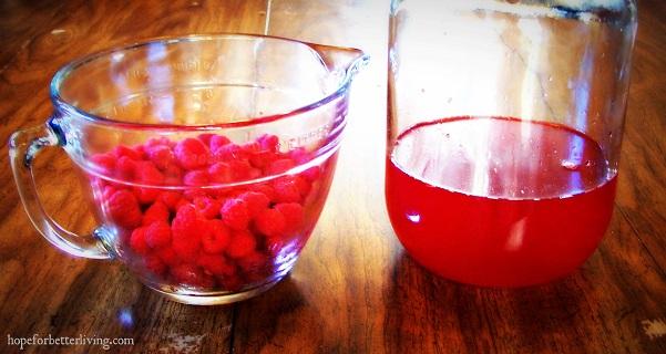 A bowl of raspberries and glass jar of raspberry vinegar.