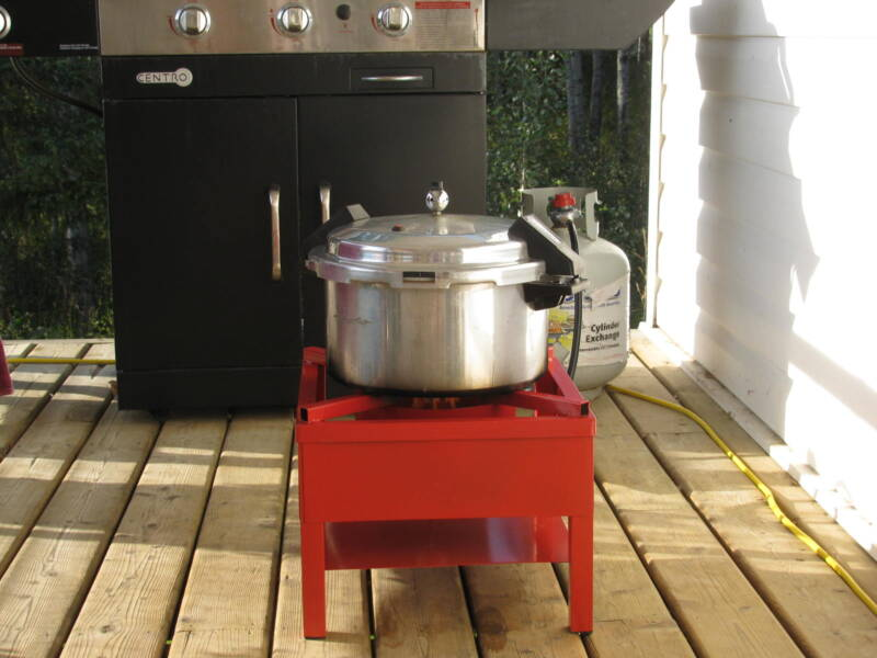 A weighted pressure canner on a propane burner