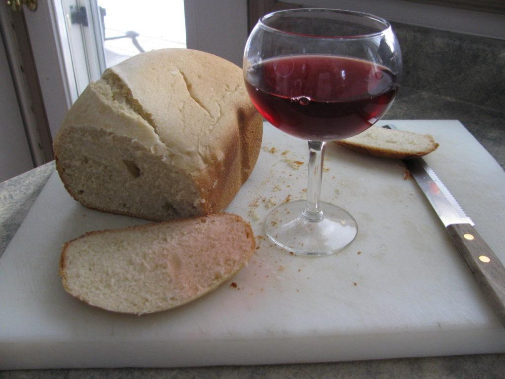 A loaf of homemade bread alongside a glass of Raspberry Wine